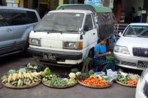 Myanmar Yangon Straßenverkäuferin zwischen den Autos